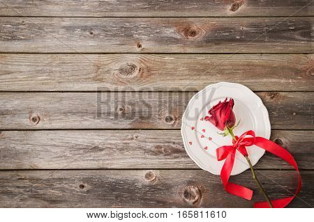 romantic table setting with a white dish and red rose