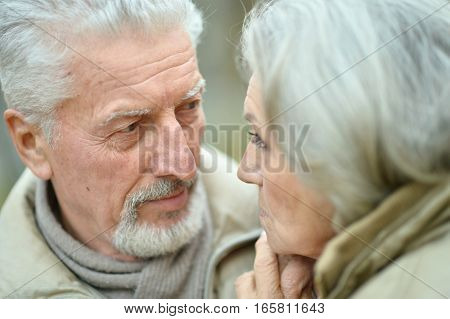 Close-up portrait of a smiling senior couple in warm clothes looking at each other outdoors