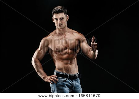 bodybuilder posing. Beautiful sporty guy male power. Fitness muscled man holding thumb up