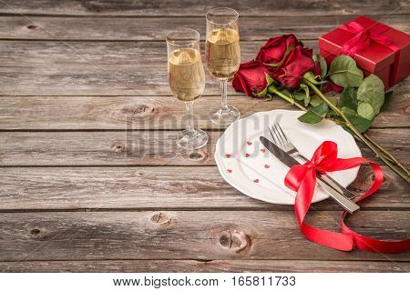 romantic table setting with a white dish roses and champagne glasses