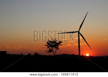 A solitary Wind Turbine silhouetted against a dramatic sunset sky.