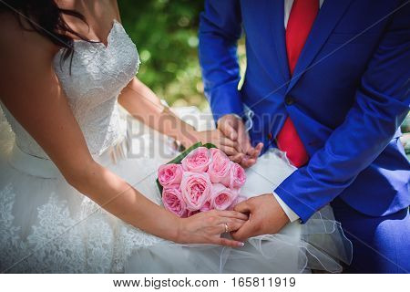 Bride and groom holding bridal bouquet close up.