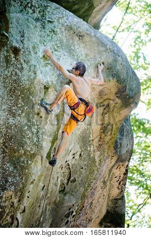 Male Rock Climber Climbing With Rope On A Rocky Wall