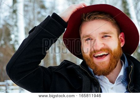 Fashion portrait handsome elegant bearded man wearing black coat in winter day over snowy trees forest background,
