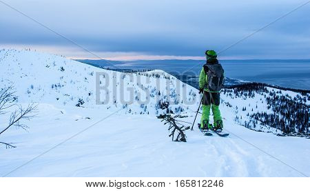 Young man on splitboard on the mountain ridge in evening light looking to horizon