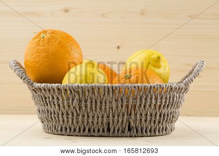 citrus fruits in the bowl over wooden background