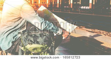 Young man backpacker waiting for train and travel bag and travel map. Travel concept.