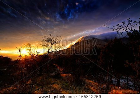 Sunset in the forest in the mountains on a glade, the sun's rays make their way through the blue clouds, the soft light from the sun at sunset, the clouds on the top of mountain, forest in the mountains at sunset