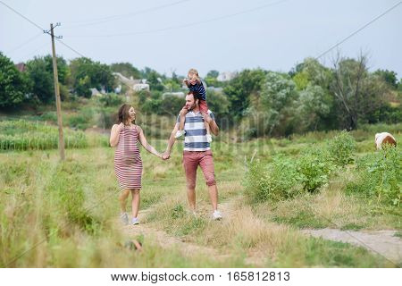 Happy pregnant family having fun in summer nature. A child on the shoulders of dad. Countryside walk along rural road. Father and mother holding hands. Parents look at each other