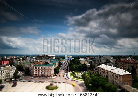 Panorama of the historic city of Kiev, views of the city from a height, small houses, churches and streets with cars in miniature, blue sky with white clouds over the city, the urban area from the height