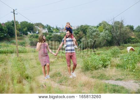 Happy pregnant family having fun in summer nature. A child on the shoulders of dad. Countryside walk along rural road. Father and mother holding hands.