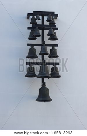 Fifteen black hand-forged bells from the smallest to the largest on a white wall