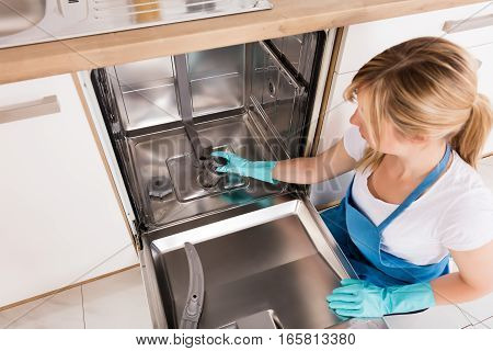 Young Woman Cleaning And Fixing Dishwasher In Kitchen