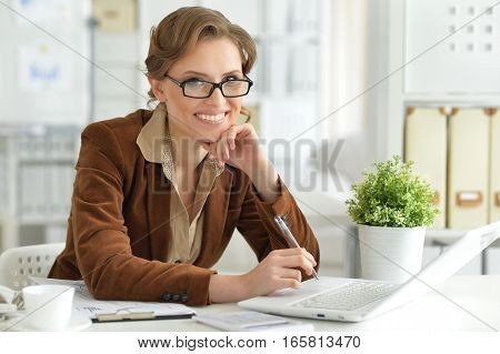 Portrait of young businesswoman working on laptop in office
