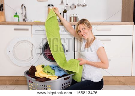 Young Woman Looking At Clean Clothes Out Of Washing Machine In Kitchen
