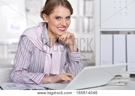 young woman working at office, using laptop
