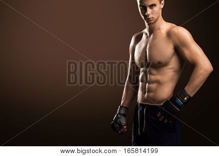 Mixed Martial Arts Fighter With Abdominal Muscles Isolated On Brown Background