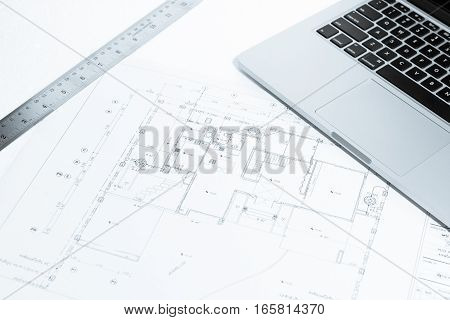 Metal Ruler And Notebook Over House Construction Blueprint With Blue Tone Effect