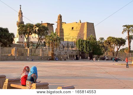 LUXOR, EGYPT - NOVEMBER 4, 2011: Two young Egyptian girls sitting in front of Luxor temple