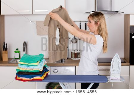 Shocked Young Woman Looking At Burnt T-shirt While Standing By Ironing Board At Home