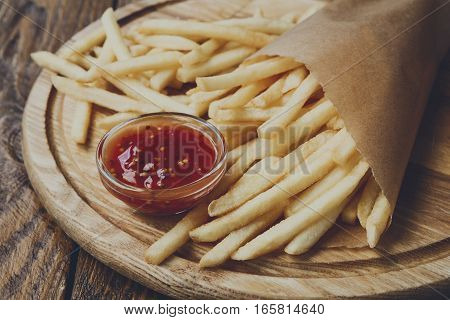 French fries wrapped in brown craft paper, closeup. Fast food take away on rustic wood. Fried potato chips with tomato sauce. Filtered