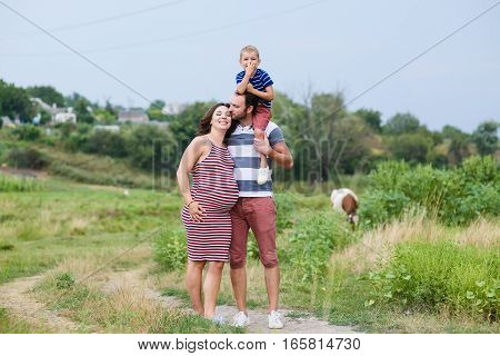 Happy pregnant family having fun in summer nature. A child on the shoulders of dad. Countryside walk along rural road. Happy pregnant family embracing