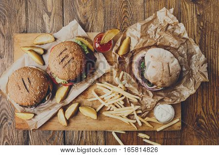 Fast food dish top view. Meat burger in craft paper, potato chips and wedges. Take away composition. French fries, hamburger, mayonnaise and ketchup sauces on wood.