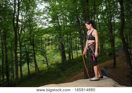 Female Climber Standing On Big Natural Boulder In The Forest