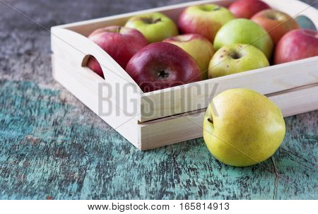 Fresh apples in a tray on a wooden background. Apples are red, green, yellow. Healthy Eating Vitamins Vegetarian Seasonal harvest.