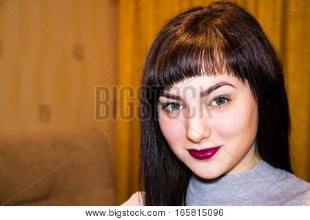 Portrait of young beautiful woman with expressive eyes and lips. On the girl's face a modest smile