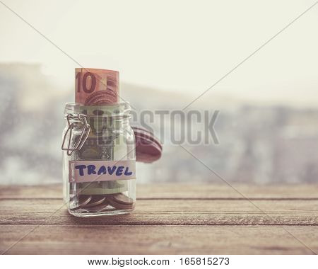 jar with money on wooden table next to window. holiday savings