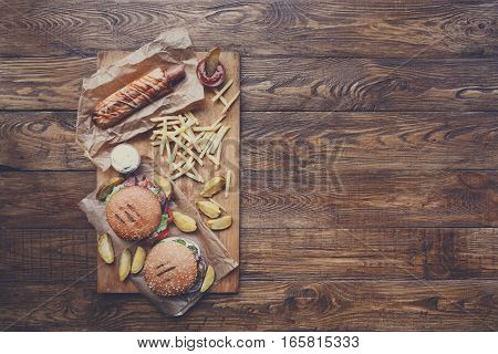 Fast food dish top view. Appetizing meat burgers, potato chips and wedges with hot dog. Takeaway composition. French fries, hamburger and sauces on wood with copy space. Menu or receipt mockup
