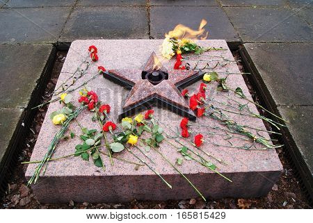 an eternal flame, red banners, veterans, spring flowers, a memorial to the fallen