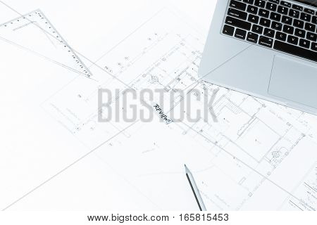 Pen, Drawing Rulers, And Notebook Over House Construction Blueprint With Blue Tone Effect