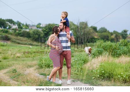 Happy pregnant family having fun in summer nature. A child on the shoulders of dad. Countryside, walk along rural road. Happy pregnant family kisses