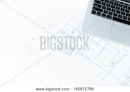 Notebook Over House Construction Blueprint With Blue Tone Effect
