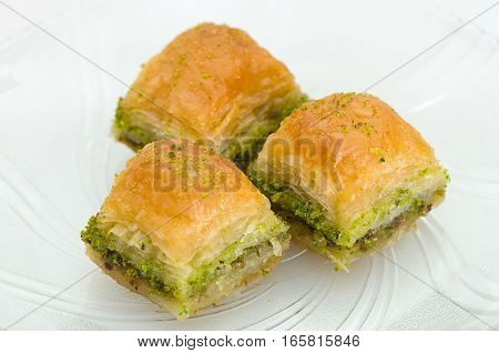 Baklava on the plate with pistachio on a white background poster