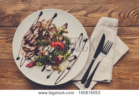 Restaurant food. Sliced meat salad with fresh vegetables and cheese on white round plate. Healthy meals on served wooden table