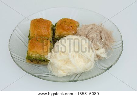 Baklava with pistachio, pismaniye on the plate on a white background