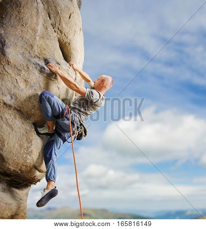 Male Climber Climbing Big Boulder In Nature With Rope