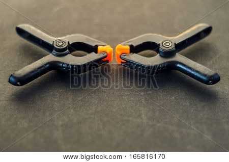Pair of black clamp with orange plastic jawson on black textured carpenter's bench. Part of the workplace of a carpenter