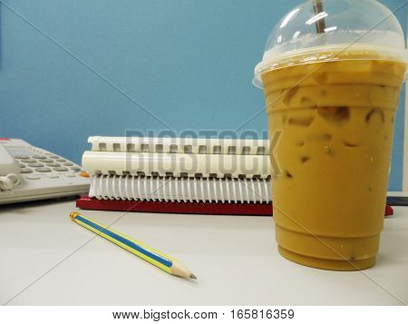 Plastic cup of coffee on table,coffee background,Cold coffee in plastic cup on white table in office. Cup of espresso coffee.