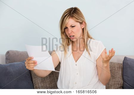 Portrait Of A Shocked And Sad Young Woman Reading Letter