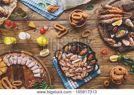 Seafood platter top view, flat lay. Mediterranean cuisine restaurant food, fried calamari rings, shrimps, mussels, oysters, shellfish delicacy on wood table background. Catering, banquet table