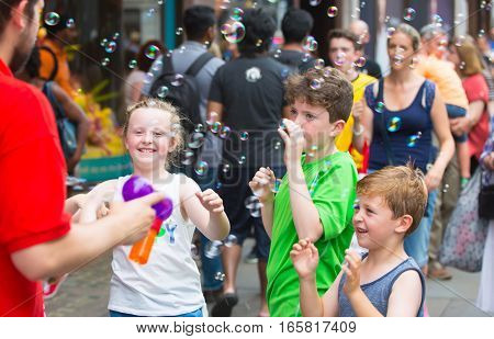 London, UK - August 24, 2016:  Kids playing with bubbles in the Regent street next to the toy shop