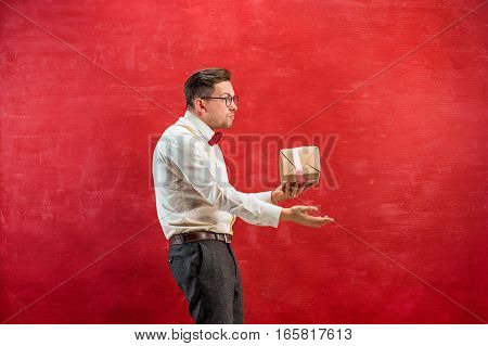 The young funny man with abstract heart on red studio background