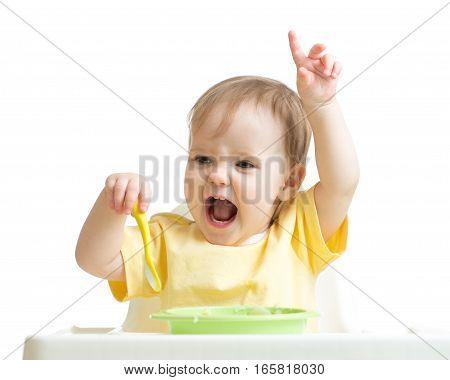 Baby girl eating her dinner isolated on white background