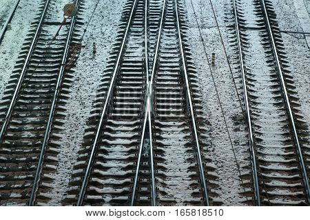 Steel railways on the winter ground with a snow.