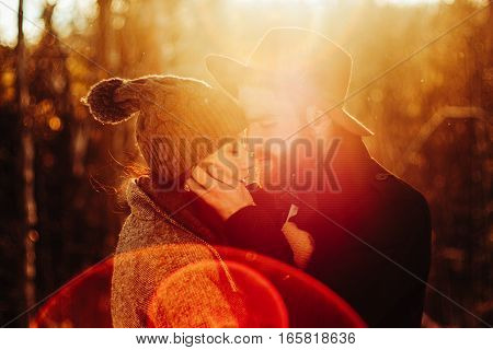 Portrait of beautiful young couple holding each other against sun flare sky, playful joyfully looking at each other with fun expressions, outdoors. Boyfriend and girlfriend winter travel lifestyle.