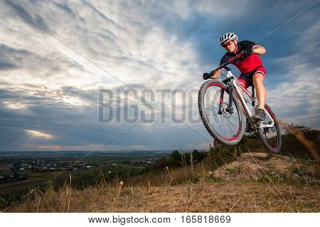 Mountain Cyclist Riding Donwhill Against Blue Evening Sky